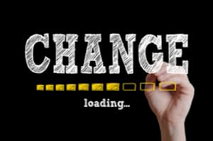 A hand writing the word change with a loading bar beneath - changes to insurance
